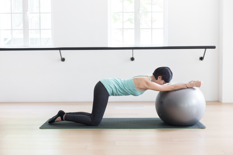 Anti-aging Pilates at Upside Motion modified cat-cow stretch with fitness ball 3
