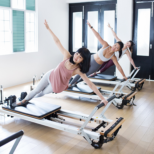 woman doing pilates reformer at upside motion